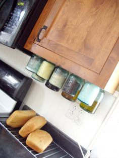 Mason jars with the lids screwed onto the bottom of the cabinet to store nonperishable essentials. Just like grandpa used to organize his workshop!