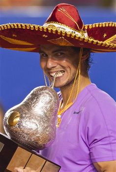 """Wearing a traditional Mexican """"sombrero"""", Spains Rafael Nadal bites the trophy for the cameras after beating Spain's David Ferrer in the final round match of the Mexico Open tennis tournament in Acapulco, Mexico, Saturday, March 2, 2013. Nadal blasted past top seed and defending champion David Ferrer 6-0, 6-2 in Saturday's final in a powerful performance that indicated he has quickly returned to near his best after a long-term knee injury.(AP Photo/Christian Palma)"""