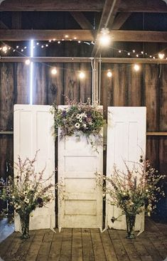 A clever way to use old doors and dried flowers to create a rustic backdrop for a photo booth or even behind a bridal table! Indian wedding decor - Engagement party decor - vintage wedding decor - rustic decor - photo booth backdrop - DIY photo booth ideas - fairy lights #thecrimsonbride #churchweddingdecorations