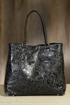 Overland Pecos embossed leather shoulder bag lights up your look with double rows of shiny metal studs on each side.