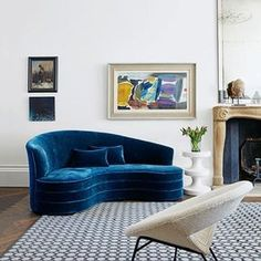 A contemporary white room with curved blue sofa. Modern and country, small and large, furniture and colours. The best living room decoration ideas from House & Garden.