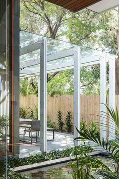 Ein Glasdach und weiße Stahlbalken formen eine Terrasse