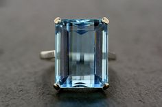 +++WE WILL BE ON HOLIDAY FROM 23RD TO 31ST MARCH. ORDERS WILL BE SENT OUT ON THE 1ST APRIL+++A simply fabulous Art Deco ring with a large, rectangular, deep-blue aquamarine that sits proud from the finger. A classic style of cocktail ring popular from the 1920s onwards. This is made from platinum, with a simple, solid setting holding the step-cut, deep stone in four claws, allowing the colour of the aquamarine to shine. A spectacular and unique statement ring. The aquamarine is a large…
