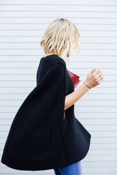 Black sweater cape. With jeans and a red clutch. A look to copy now if you have a date waiting for you.