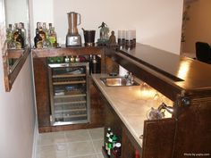 A man cave bar area with a sleek mini refrigerator, tan countertops and tile flooring.