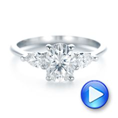 #103035 This elegant engagement ring features an oval diamond in the center of a three-stone setting, with a pear shaped diamond on either side. It's a classic and timeless...
