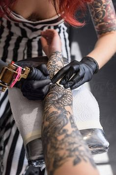 Close-up of artist tattooinarm by Milles Studio for Stocksy United. Crop shot of female master in black gloves tattooing arm of anonymous client on clean pad in salon.