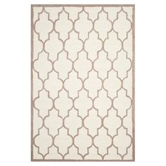Wool rug in ivory and beige with a quatrefoil trellis motif. Hand-tufted in India.   Product: RugConstruction Materi...