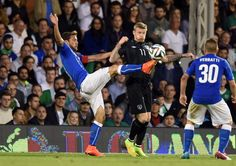 Claudio Marchisio of Italy and James McClean of Ireland compete for...