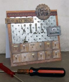 Distressing techniques and Mr Smith's Workshop are a match made in papercraft heaven! This speedy make by PDT member Mags Woodcock cleverly uses mirror board, debossing, sandpaper and paint to create a life-like workshop pegboard, fit for all DIY-lovers out there.