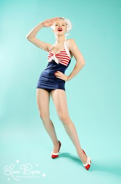 """Bettie """"Hello Sailor"""" Swimsuit - Inspired by our love of Vargas and Petty Pinups, the Bettie Swimsuit is the ultimate pinup girl bathing suit! Featuring a sexy, skirted bottom, a gathered bodice, and contrast halter straps.  Features Include:Fully lined inside front to define your curvesTop is lined (no cups), and has a built-in shelf bra to lift that cleavageAdjustable tie halter straps accommodate all bust sizes."""