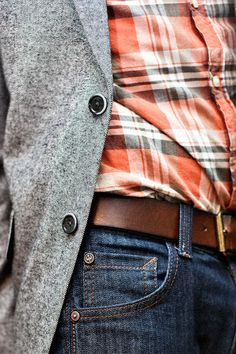 Comprar ropa de este look: https://lookastic.es/moda-hombre/looks/blazer-gris-camisa-de-manga-larga-naranja-vaqueros-azul-marino-correa-marron/819 — Blazer Gris — Camisa de Manga Larga de Tartán Naranja — Correa de Cuero Marrón — Vaqueros Azul Marino