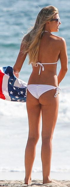 All-American: The 25-year-old Elite Model rocked a white string bikini while clutching a towel, two tiny flags, and a pair of sunglasses emblazoned with the States' stars and stripes