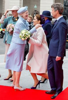 Crown Princess Mary curtsying to her mother-in-law, Queen Margrethe, when she arrives as the last one outside the Danish Parliament.