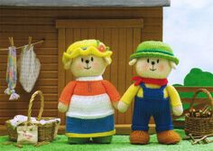 """'Country Boy and Girl' from Jean Greenhowe's 'Playful Puppies' pattern booklet. Working outdoors has given these pups a rosy glow. Knitted in DK they are easy to make and are 21cm/8.25"""" tall (excl hats). The booklet was published in 2013."""