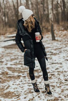 White pom pom beanie, black long puffer jacket, black sweatshirt, black moto leggings, cream wool socks, black snow boots, black aviator sunglasses.