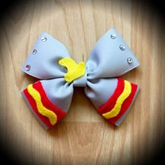 Dumbo Disney Character Inspired Grey Hair Bow.  Grey Grosgrain Ribbon Decorated with Yellow and Red Felt Accents, Yellow felt hat detail and rhinestones.  Mounted on an alligator clip.  I can do custom bows, just let me know if youd like something specific.  Price is for single bow.