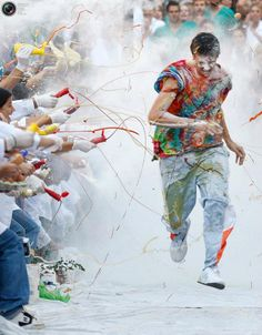 A faculty of medicine first year student runs while seniors spray him with different types of sauces.  Granada,Spain