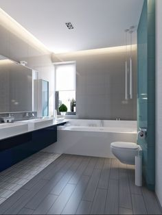 The mostly neutral house gets a burst of color from the vibrant blue secondary bathroom with light blue glass tiles behind the toliet and sleek modern cabinetry under the dual sink vanity.