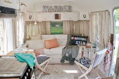 """Sarah's Airstream was dark when she purchased it, but she quickly painted everything white, and installed hardwood floors. """"I salvaged the original sofa and recovered it in bleachable indoor and outdoor linen,"""" she writes. """"The wandering star pillow was my inspiration for the interior. I fell in love with the phrase, and the colors, and the term 'wander' began to appear throughout the design."""" RELATED: 14 Gorgeous Camper Decorating Ideas"""