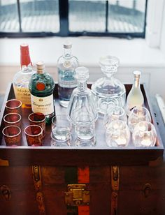 makeshift bar cart....tray on vintage suitcase..will be scouring yard sales and flea markets for an old trunk.