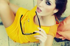 Woman modeling a yellow dress with glasses and dramatic eye make up