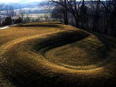 Serpent Mound, Ohio (by Krista Backs) - Serpent Mound, Ohio. It was first positively dated and attributed to the Native American Adena culture (c. 800 BCE - 1 CE) but later excavations strongly suggested it was built by the natives of the so-called Fort Ancient culture (c. 1000-1750 CE) and, most likely, around 1070 CE.