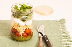 Salada Caprese no Pote Ingredientes 1/2 xícara (chá) de macarrão tipo fusili 8 tomates grape 8 minimuçarelas de búfala 1 xícara (chá) de folhas de rúcula baby 1/2 xícara (chá) de manjericão fresco 1/4 xícara (chá) de castanha-de-caju 1 dente de alho 3 colheres (sopa) de queijo parmesão ralado 1/4 xícara (chá) de azeite 1 cubo de gelo 1 colher (chá) de vinagre sal e pimenta-do-reino moída na hora