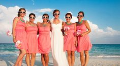 Bridal party in pink bridesmaid dresses, teal accessories and sunglasses on the beach | Palace Resorts Weddings ®