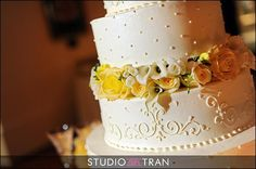 Royal Cakery--Scroll Work & real flowers.  Love the scrolls on one layer with swiss dots on the next!