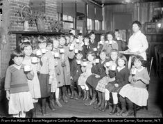 Edward Mott Moore Open Air School. Located in the former club house of the Rochester Rod & Gun Club, the building has been remodeled to be used as the city's only open air school for children at risk for tuberculosis. The children, gathered in front of the fireplace, hold up the cups of milk that are provided as part of their health treatment. Many of them wear warm sweaters. Rochester NY