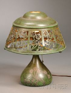 Heinz Art Table Lamp  Mixed metals  United States, c. 1920  Domed shade with openwork panels of flowers and vines, cloth backing missing, on three-arm spyder, single socket with narrow neck on bulbous base with conforming silver overlay decoration, the whole in patinated verdigris finish.