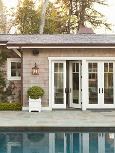 Peaceful - slate pool surround, shake shingles with white trim, white Versailles planter. Two-over-one windows and French doors leave views uninstructed. Pool-house by Lee Ann Thornton ✨these French doors Exterior Design, Interior And Exterior, Exterior Doors, Piscina Interior, Cottage Living, Pool Houses, Home Fashion, Style At Home, French Doors