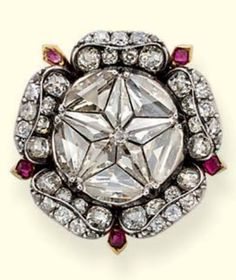 A VERY RARE ANTIQUE DIAMOND BROOCH. The vari-cut diamond rosette to the later 19th century diamond rose petal surround with ruby detail and pendant fitting, mounted in silver and gold, rosette probably early 16th century, surround circa 1830.