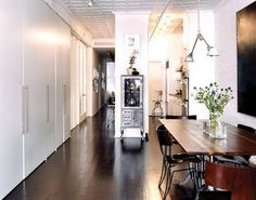 dark wooden table, dark floors, white walls, flowers