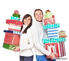 Happy young couple carrying Christmas gifts www.teelieturner.com #Christmas