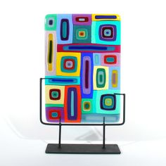 """Fused glass sculpture.17.5"""" H x 17"""" W x 4"""" D, opaque and transparent glass with iron stand.  Technique: Multiple layers, fused. Carlyn Gallery"""