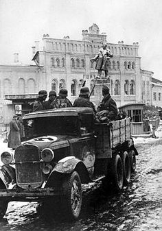 German soldiers riding in a captured GAZ-AAA truck past the monument of V. I. Lenin in an occupied Soviet city.