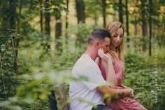 Woman sitting on her fiancé's lap in the woods