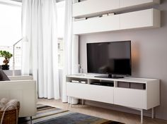 A living room with wall cabinets and a TV bench, all in white