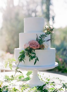All white flower embellished three tier wedding cake: http://www.stylemepretty.com/2016/08/18/escape-to-the-hills-of-carmel-valley-with-this-inspo/ Samantha Kirk - http://www.samanthakirkphotography.com/