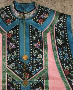 """Detail of pink Chinese vest with embroidered floral and geometric designs on silk. Has four gilt brass buttons with bird and tree designs. Buttons marked """"Treble Gilt"""" on back. Has a small tag on inside back that indicates """"China."""" 2 of 2 photos."""