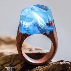 """This past spring we became enamoredwith the handcrafted accessories of Secret Wood, a Canadian shop that encases tiny, exquisite worlds in rings made of clear resin and wood. Their beautiful designs feature mystifying places where miniature mountains and caverns are revealed beneath snow-speckled skies. Secret Wood has since continued to create gorgeous rings with new """"places"""" that reflect the vibrancy of the season. The updated designs highlight the warm weather and all that it brings…"""