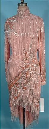 """1980s BOB MACKIE Pink Fully Beaded Dress, """"v"""" hemline, short in the front and long in the back with clear beaded fringe all around the scalloped hemline. Pink, silver, white, and coral beads and sequins create the rest of the deco and floral design."""