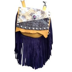 "PURPLE MAGIC MARTY - velvety soft, made of gold deerskin with a 7"" purple deerskin fringe. The silver centerpiece is intricately carved, with a cut purple jewel-like crystal center. It's surrounded by a beautiful floral printed leather and genuine gator. Etched silver metal studs outline the flap. Wear bag clipped to belt loops for hands-free carrying of your essentials. Interior includes a leather strap. Add the strap when you want a completely different look."