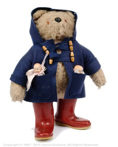 A Gabrielle Designs Paddington Bear, blue duffle coat and red size 5 Dunlop Wellington boots; with a pair of modern bisque baby dolls- one in each pocket