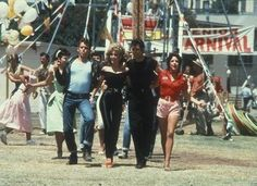 """From left, actors Jeff Conaway, Olivia Newton-John, John Travolta and Stockard Channing walk arm in arm at a carnival in a still from the 1978 movie musical """"Grease. Olivia Newton John, John Travolta, Film Scene, Jeff Conaway, Movie Stars, Movie Tv, Movie Theater, Theatre, Grease 1978"""
