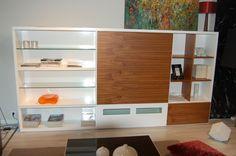 """Librería de salón lacada en blanco de alta calidad, diseño italiano, con puerta corredera en nogal natural. Puertas con sistema de """"push"""" y  baldas interiores en cristal."""