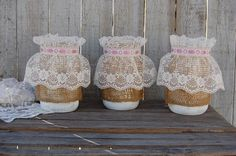 3 shabby chic mason jars hand painted in soft white, lightly distressed and wrapped with burlap, white lace with pink ribbon and a protective coating. They are
