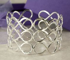 Statement sterling silver wide cuff bracelet with an infinity/figure of 8 design.  By Jayne at Woven Art Jewellery.       www.wovenartjewellery.co.uk